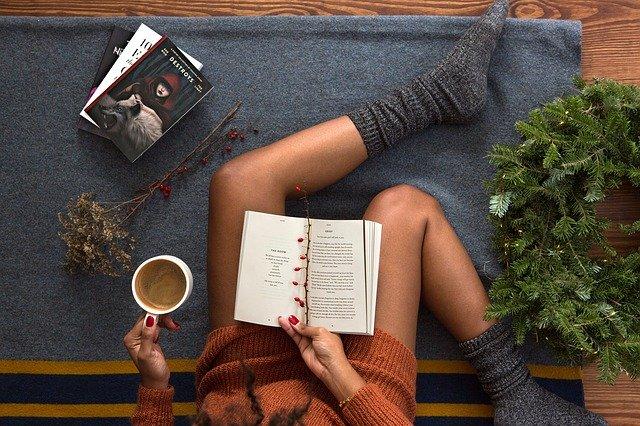 čtení knihy, žena sedí a v klíně má otevřenou knihu